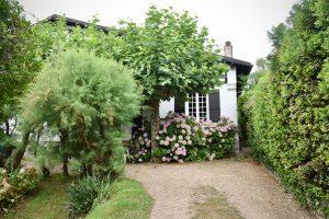 Bild vor einem idyllischen, weißen Haus mit rosa Blumen und Bäumen